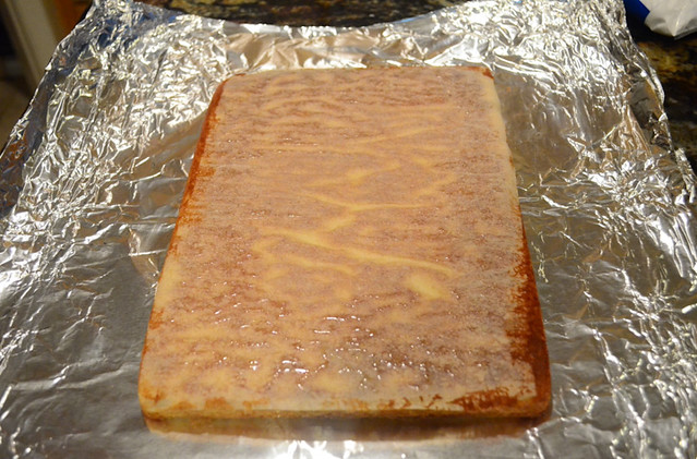 The baked cake has been removed from the cake pan and is placed upside down on a sheet of aluminium foil with the parchment paper on top.