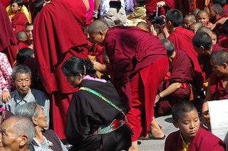 Waiting for photos: young Sakya encarnate lama, Tibetan Buddhists in front of Tharlam Monastery, monks in red and maroon robes, a Tibetan woman wearing a formal black chuba and belt, Lamdre, Boudha, Kathmandu, Nepal
