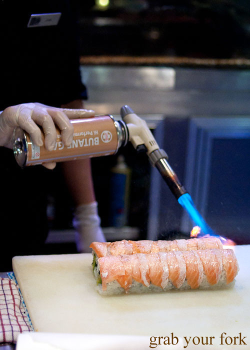 Blow torching salmon at Umi Kaiten-Zushi
