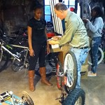 Mr. Vic working with Lesley and Jamira in the Makerspace bike shop.