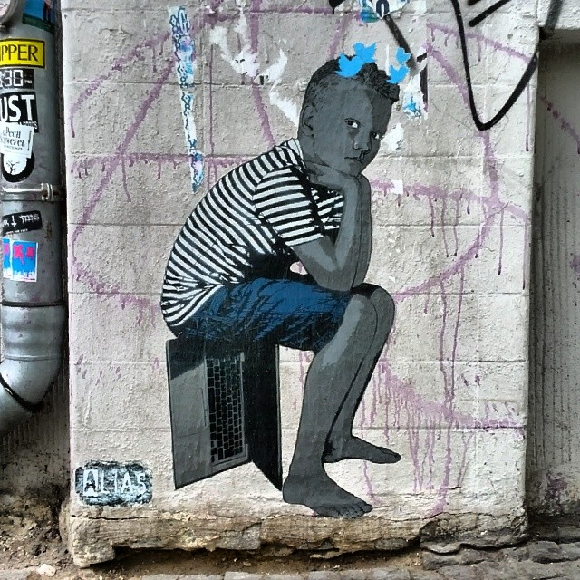 Street art depicting a boy in a striped shirt sitting on a partially open laptop computer