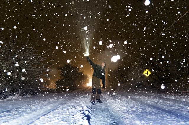 Long exposure showing motion of snow falling lit by flashlight AND on-camera flash freezing motion of snow falling at night