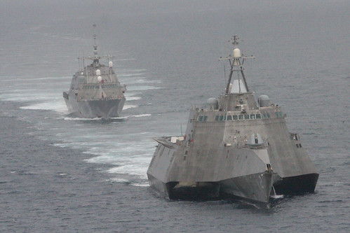 The first of class littoral combat ships USS Freedom , rear, and USS Independence maneuver together during an exercise.