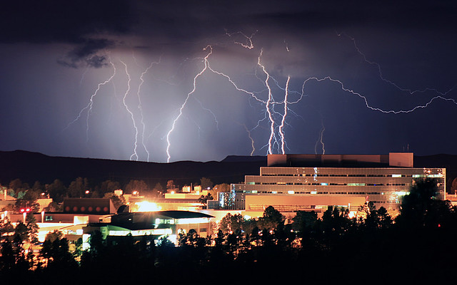 An electrical storm near Santa Fe lights up the summer night sky behind Lab buildings at Technical Area 3.  Photo by Ethan Frogget