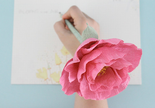 hand writing with a pink crepe paper peony affixed to an ink pen