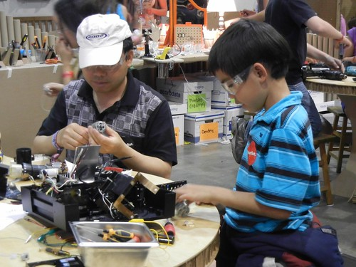 man and kid tinkering together