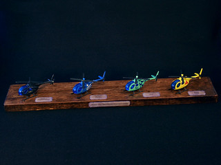 colorful toy helipoters on a wooden display stand