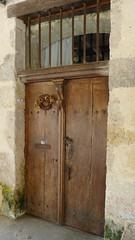 Vieille porte en bois sous les arcades à Fourcès
