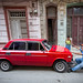 Cuban repairing his red Lada, vintage Russian car worth 20k USD in Cuba