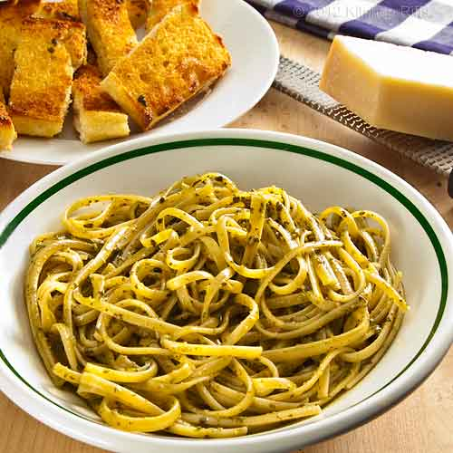 Pesto Pasta with Garlic Bread and Parmesan Cheese in Background