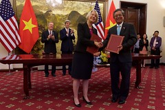 Peace Corps Director Carrie Hessler-Radelet poses for a photograph after the signing of a historic partnership to establish a Peace Corps program for the first time in Vietnam, as U.S. Secretary of State John Kerry and U.S. Ambassador to Vietnam Ted Osius stand behind her, at the Ministry of Foreign Affairs in Hanoi, Vietnam, May 24, 2016. The announcement of the partnership coincides with U.S. President Barack Obama's trip to Vietnam and underscores the United States' broader commitment to supporting the people of Vietnam through English language learning. [State Department photo/ Public Domain]