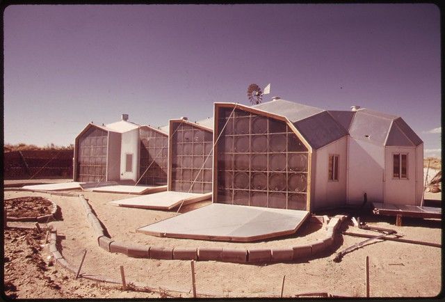 Exterior picture of the south facing walls of a modular solar-heated home near Corrales, New Mexico. The panels are dropped during the day to allow sun to pass through the glass and heat water in blackened 55-gallon drums, 04/1974 Documerica by Boyd Norton.