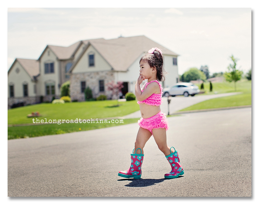 FIngers in mouth walking across the driveway in her ruffles and boots BLOG