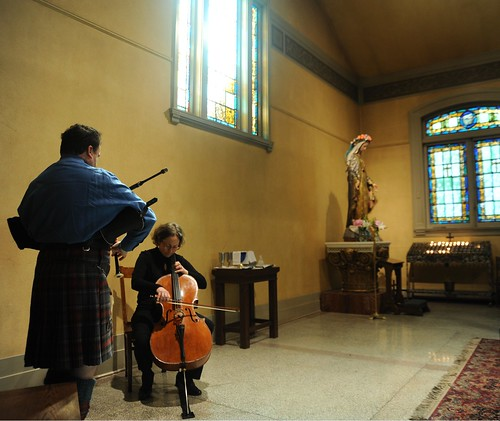 Bagpipe player and cellist, statue of Mary, votive candles, stained windows, rug, St. James Cathedral, First Hill, Seattle, Washington, USA by Wonderlane
