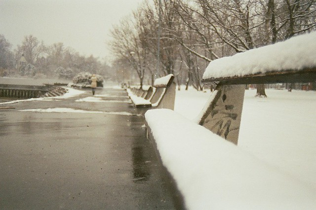 Budapest, city, streets, tour, trip, journey, Hungary,  snow, winter, spring, 35mm film photography,  Kodak MAX 400 expired, girl walking away, cold, wintertime, park, bench, snow, heavy snow on benches, jacket