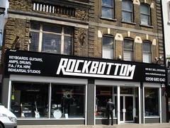 "A double-width terraced shopfront in black, white, and grey.  The sign above reads ""Rockbottom"" in capital letters with the R and M joined via an underlining of the intervening letters.  To the side of this sign, text reads ""Keyboards Guitars, Amps, Drums, P.A./P.A. Hire, Rehearsal Studios"".  Guitars, amps, a drumkit, and a yellow ukulele are visible in the large shop windows.  A person in black jeans and a black leather jacket is looking into the windows."
