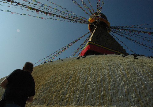 Prayers at the dome of Bodha's great wish-fulfilling stupa, pigeons, whitewash, prayer flags, Bodha, Kathmandu, Nepal by Wonderlane