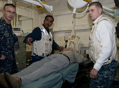 PACIFIC OCEAN (June 4, 2012) Lt. Cmdr. Ron McGuire. left, Lt. Cmdr. Adnan Jaigirdar, and Hospital Corpsman 3rd Class Matthew Williams, right, evaluate a 60-year-patient aboard amphibious assault ship USS Peleliu (LHA 5). (U.S. Navy photo by Mass Communication Specialist Seaman Jasmine Sheard)