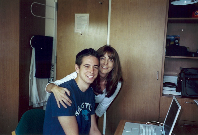 Valerie posing with Boy#1 in a college dorm room.
