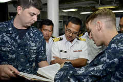 Electronics Technician 1st Class Benjamin Smith, left, and Senior Chief Sonar Technician (Submarines) Jake Jaegar, right, explain the purpose of certain technical work documents to officers of the Royal Malaysian Navy (RMN) as part of a Quality Assurance Submarine Safety Program (SUBSAFE) seminar aboard USS Frank Cable, April 15. (U.S. Navy/MC1 Brandon Shelander)
