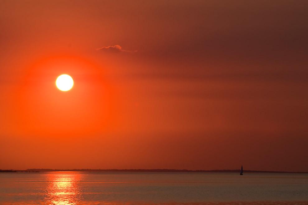 En la víspera de la semana santa, el sol cae mientras un barco velero sigue estacionado en las aguas del Río Paraná en las cercanías de la costanera de Encarnación. (Elton Núñez)