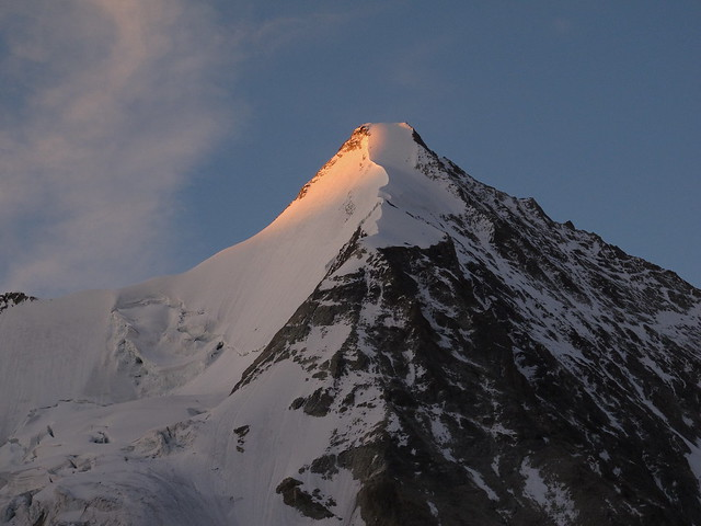 The first rays of the morning sun illuminate the summit of Obergabelhorn