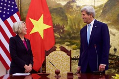 Peace Corps Director Carrie Hessler-Radelet and U.S. Secretary of State John Kerry share a smile at the signing of a historic partnership to establish a Peace Corps program for the first time in Vietnam, at the Ministry of Foreign Affairs in Hanoi, Vietnam, May 24, 2016. The announcement of the partnership coincides with U.S. President Barack Obama's trip to Vietnam and underscores the United States' broader commitment to supporting the people of Vietnam through English language learning. [State Department photo/ Public Domain]