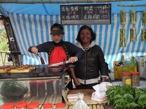 利用假日來幫忙的部落女生,正煮著由媽媽製作的馬告香腸及烤肉。