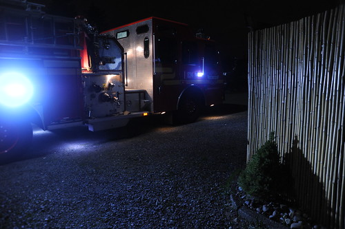 Night fire truck trauma rescue, blue lights, bamboo fence, Italian tree, gravel driveway, Seattle, Washington, USA by Wonderlane