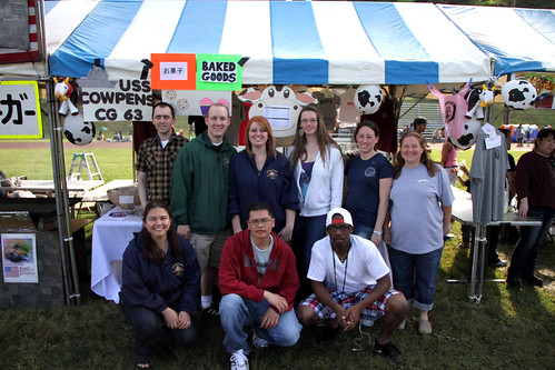 USS Cowpens (CG 63) and family members pose in front of the Cowpens Ikego Friendship Day Festival booth.