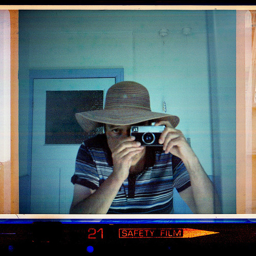 reflected self-portrait with Kodak Instamatic 233-X and floppy hat by pho-Tony