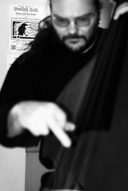 A blurry black and white shot of Wulf playing double bass with the focus on a poster in the background