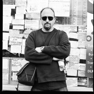 a black and white photo of Louis CK against a wall