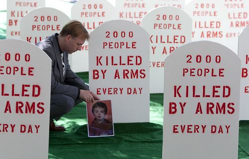Control Arms campaigner David Grimason lays a photo of his son Alistair, who was killed by stray bullets in a gun fight, at the base of a mock tombstone. Control Arms coalition set up a mock graveyard next to the United Nations building in New York July 25, 2012. They are demonstrating as the negotiations for an Arms Trade Treaty comes to a close on Friday. Image and caption courtesy Control Arms/ Andrew Kelly