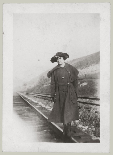 Girl with hat on the railroad tracks