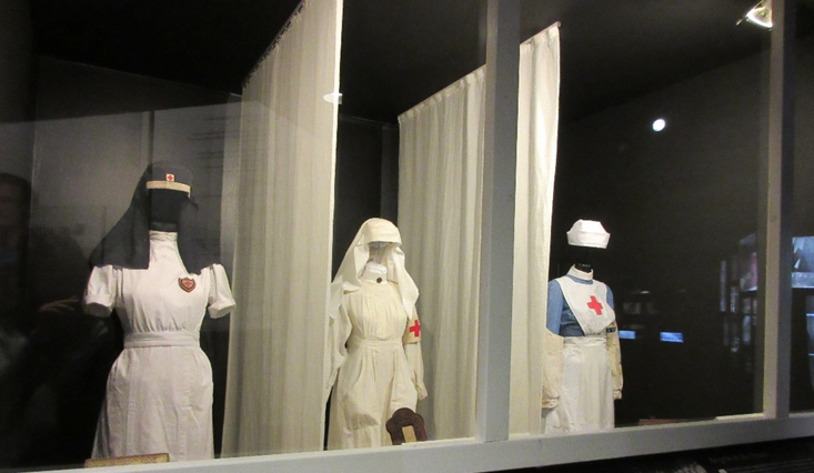 WWI nurses' uniforms on display at a museum with the IJzertoren.