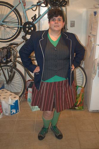 fat girl with short, asymmetrical curly hairdo in a green shirt, pinstripe vest, navy jacket with white piping, brown and rust striped skirt, green socks and houndstooth converse with green laces. Her finger nails are half houndstooth with a green stripe at the bottom of the pattern.