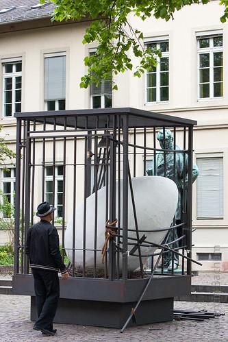 Foto eines zerstörten Käfigs mit einem überdimensioniert großen Ei. Ein Mann steht davor und schaut.