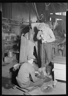 The flint glass shop showing a blower rotating a bottle as he blows it in an iron mould, March 1937