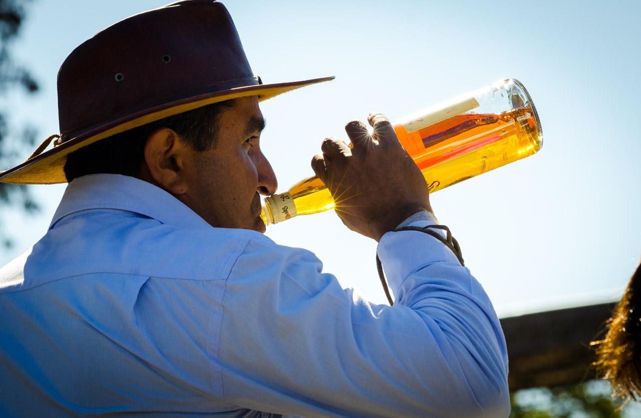 Un jinete bebe tragos de wiski mientras espera su turno para ser presentado en el desfile de caballerías durante la fiesta del Ovecha Rague el pasado 12 de junio en la ciudad de San Miguel, departamento de Misiones. (Elton Núñez)