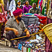 A man crouches by his wares in a street market Delhi