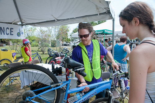 A volunteer helps a cyclist at the Bike Maintenance tent.