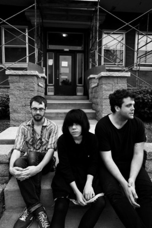 the members of screaming females sitting on steps looking pensively into the camera, as one member gazes into the distance