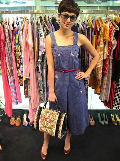 'Allo miss! Where you going? You look very chio leh.  We love this denim dress (Size S/M) with little plaid accents - comes with its own maroon skinny belt. Worn with Etienne Aigner slingback heels, a gorgeous embroidered bag from Western Germany, and green Mondi shades (NOS).