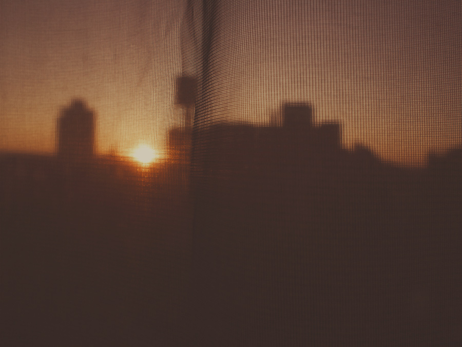 Brooklyn water coolers at sunrise through a gauzy blind
