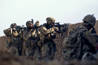 U.S. Army Soldiers firing over a wall.