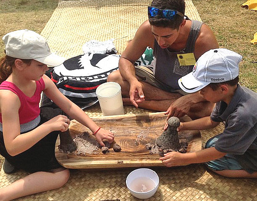 <p>Loi Assistant Kaulana Vares, of the University of Hawaii at Manoa's Ka Papa Loi O Kanewai, teaches youngsters to pound taro at the University of Hawaii exhibit at the Smithsonian Folklife Festival.</p>