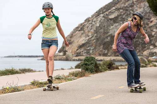 """Two female skateboarders - T-shirt says """"Reading is Sexy. On the return on the harborwalk path with Morro Rock and the harbor entrance in the background, two girls (most participants were male). 2012 2nd Annual Morro Bay Mile Skateboard Race,"""