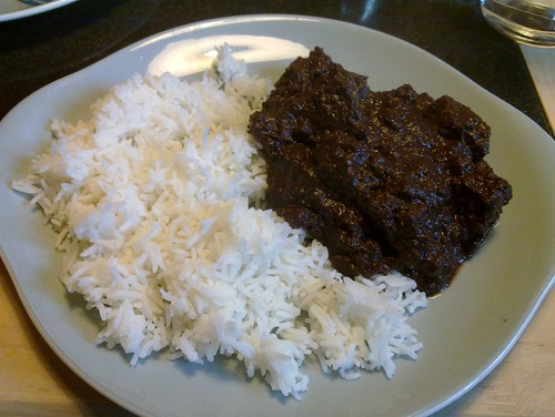 A pale blue plate filled around two-thirds with white rice and one-third with a very dark, thick stew.