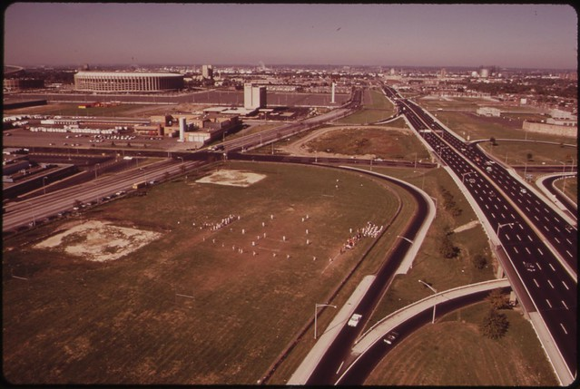 Philadelphia Junior High School Football Team Plays On Field Surrounded By Freeways. Municipal Stadium In Left Background, August 1973 by Dick Swanson for Documerica.